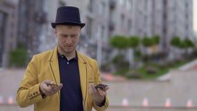 Illusionist в шляпе и желтой куртке умело двигая играя карточки в руках сток-видео