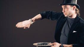 Illusionist принимает карточки от воздуха и бросает их в верхнюю шляпу сделанную карточек сток-видео