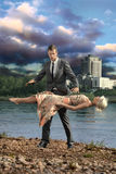 Illusionist. A handsome confident man keeps a young lady levitating in the air Royalty Free Stock Photo