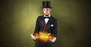 Illusionist conjure with his hand gambling staffs. Young illusionist in tails hold between hands gambling staffs with super power royalty free stock images