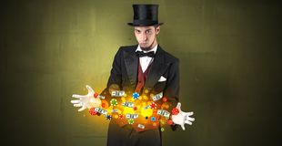 Illusionist conjure with his hand gambling staffs. Young illusionist in tails hold between hands gambling staffs with super power royalty free stock photography