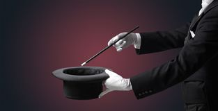 Illusionist hand want s to conjure something. Illusionist white hand wants to conjure with magic wand from a black cylinder something stock image