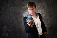 Illusionist man makes smoke his hand. On a dark background stock photo