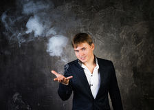Illusionist man makes smoke his hand. On a dark background stock photos