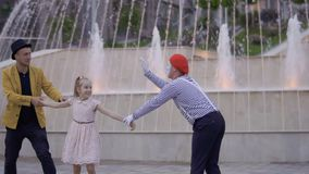 Magician get win in fight with mime. Illusionist and mime are showing performance at the urban street near fountains with illumination. Two artists fights for stock video