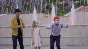 Magician and mime show their skills to little girl. Illusionist and mime are showing performance at the urban street near fountains with illumination. Two stock footage