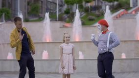 Illusionist and mime try to pay girl`s attention on himself. Illusionist and mime are showing performance at the urban street near fountains with illumination stock video