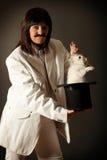 Illusionist mit Kaninchen im schwarzen Spitzenhut Lizenzfreie Stockfotos