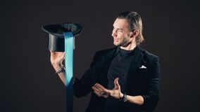 Illusionist is taking a long multicolored ribbon out of his hat. 4k stock video