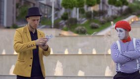 Illusionist throws playing cards into mime. Mime and magician compete who is better. Two street actors have fun together and show each other their professional stock video