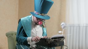An illusionist writes on a typewriter holding a candle 4k stock video