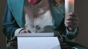 An illusionist writes on a typewriter holding a candle 4k stock video footage