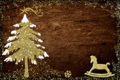 Illustrated Christmas tree and rocking horse. Illustrated green and gold Christmas tree and rocking horse on wooden background with border and copy space Stock Photo