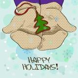 Illustration avec des mains dans des mitaines tenant la babiole d'arbre de Noël Image libre de droits