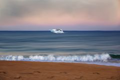 Beachfront with a boat passing in the distance. Illustration of a beautiful beach and a speedboat passing far away on the horizon royalty free illustration