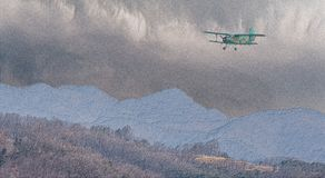 Illustration of biplane flying over rough mountainous terrain. With storm clouds building above mountains in background Royalty Free Stock Photo
