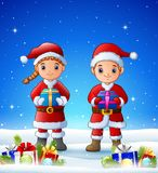 Cartoon boy and girl bringing gift box in the winter. Illustration of Cartoon boy and girl bringing gift box in the winter background with balls Stock Photo