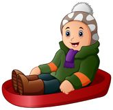 Cartoon boy in green winter clothes playing a sledge. Illustration of Cartoon boy in green winter clothes playing a sledge Royalty Free Stock Photo