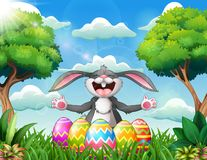 Cartoon rabbit laughing with five decorated easter eggs in the park vector illustration