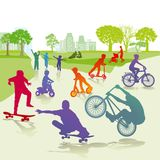 Children with skateboards and bicycles Stock Photos
