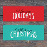 Illustration of colorful paper cards with Happy Holidays and Mer. Ry Christmas lettering. Christmas calligraphy on wood background. Vector banners. Xmas Stock Photo