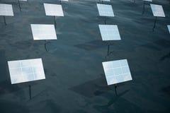 illustration 3D de grands panneaux solaires sur la mer, l'océan ou la rivière Réflexion des nuages sur les cellules photovoltaïqu Photographie stock libre de droits