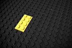 Illustration 3d: Gelbe verschiedene Spielwaren bessern Lügen auf einem schwarzen Hintergrund werden eingefügt in die Nut aus Gesc Stockfotografie