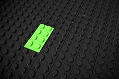 Illustration 3d: Grüne verschiedene Spielwaren bessern Lügen auf einem schwarzen Hintergrund werden eingefügt in die Nut aus Gesc Stockfoto