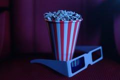 illustration 3D med popcorn, exponeringsglas 3d och stolar, med blått ljus Begreppsbiokorridor och teater Röda stolar i vektor illustrationer