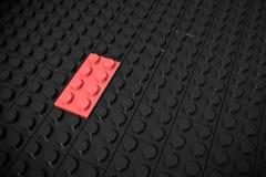Illustration 3d: Rot, das verschiedene Spielwaren Lügen separat auf einem schwarzen Hintergrund ausbessern, wird in die Nut einge Stockbild