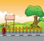 Ein hölzernes Schild und ein großer Baum Lizenzfreies Stockbild