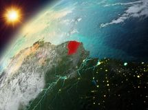 French Guiana on planet Earth in sunset. Illustration of French Guiana as seen from Earth's orbit during sunset. 3D illustration. Elements of this image Stock Photography