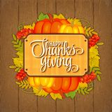 Illustration of greeting card for Thanksgiving with pupmkin and autumnal leaves on wooden background.  Royalty Free Stock Photography