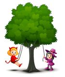 Halloween kids costumes play under the tree Royalty Free Stock Image