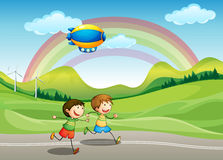 Kids running with an airship above Royalty Free Stock Photos