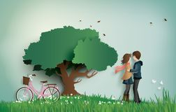 Illustration of love and valentine`s Day, with couple standing hugging on a grass field. With pink bicycle and big tree.paper art style stock illustration