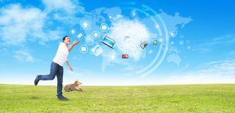 Man juggling with modern technology. Man and dog in a field juggling with laptop computer and mobile phone, modern technology concept Royalty Free Stock Images