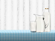 Illustration of organic milk in transparent glass, bottle and jug standing on a table covered by blue checkered napkin Stock Image