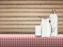 Illustration of pure organic milk in transparent glass, bottle and jug standing on a table covered by red checkered napkin Stock Photography