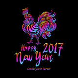Illustration of a rooster with spread wings colored rainbow colors on a dark background. Below the colored text 2017 Happy new year art Stock Illustration