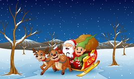 Santa claus and elf sliding in the snowing hill Royalty Free Stock Images