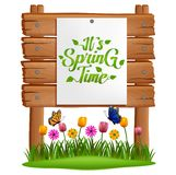 Text it`s spring time on paper stuck to a wooden board with grass and flowers . stock illustration