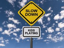 """Slow down kids playing. An illustration of a traffic sign with the text """"slow down kids playing Stock Image"""