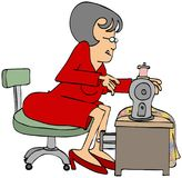 Seamstress sitting at a sewing machine Royalty Free Stock Images