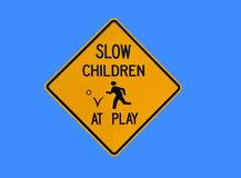 Children at play sign. An illustration of a yellow warning sign with the text slow children at play isolated on a blue background Stock Image