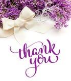 Illustrationen av buketten från lila liljor med ramen och text tackar dig Attraktion för kalligrafibokstäverhand Royaltyfria Foton