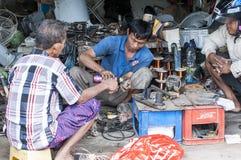 Illustrative editorial image. Poor garage owner mechanic repairing something on the floor stock photo