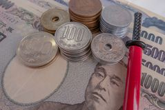 Illustrative editorial of Japanese Yen in notes and coins and a miniature katana in red scabbard.  stock images