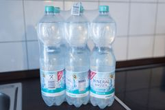 Illustrative editorial of sixpack of 1.5 liter nonrefillable PET deposit bottles. Of EDEKA sparkling mineral water in shrink wrap on kitchen counter taken in Royalty Free Stock Images
