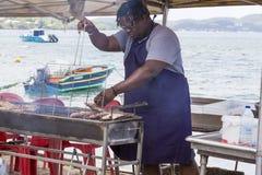 Illustratives redaktionelles Bild Ein Fisch grillt auf dem Strand Stockfotos